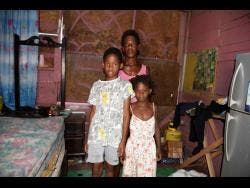Jasmine Gillepsie (centre) said that her three children have not attended school since last March.  Here, two of her children, Kobe Dixon (left) and Kimona Grant (right), stand with her in their Frog City house.
