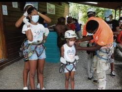 Mom, Toni (partially hidden) helps birthday girl, Tori, to get ready for the zip line, while little Teahira gets help from a Chukka team member.