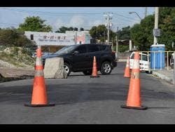 The entrance to Denham Town was blocked by the police on Monday, 24 hours after the shooting death of Harry 'Harry Dog' McLeod along Darling Street in the vicinity of Coronation Market in western Kingston.