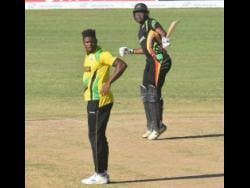 Guyana Jaguars' Christopher Barnwell celebrates scoring his century against the Jamaica Scorpions as fast bowler Oshane Tomas looks on in their Regional Super 50 encounter at the Coolidge Cricket Ground yesterday.