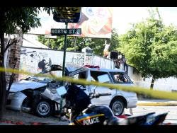 Police cordon off the scene where this Nissan AD wagon crashed at the intersection of North Street and South Camp Road yesterday in Kingston.