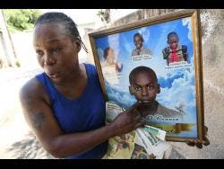 Marsha Finn shows a photo of her son, Jahime O' Connor, who was murdered in 2017.