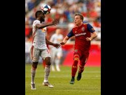 FILE New York Red Bulls defender Kemar Lawrence  heads the ball in front of Real Salt Lake forward Corey Baird during the first half of an MLS match in  June  2019.