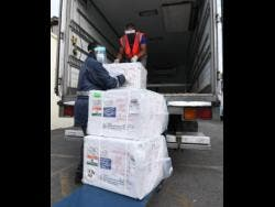 Staff of the National Health Fund removing boxes of the COVID-19 vaccine at the organisation's warehouse on Monday.