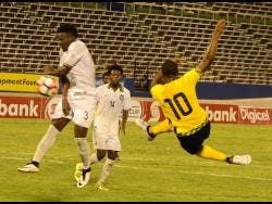 FILE Romario Williams (right) kicks the ball on the volley pass Joel Baja(left) and Sergio Eduard (centre) from Suriname during the Caribbean Cup qualifier at the National Stadium in 2016.