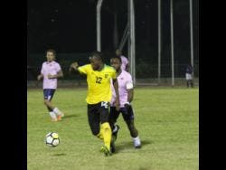 File Jamaica forward Kemar Beckford (front) dribbles the ball away from Bermuda player Cecoy Robinson during their international friendly match at the Montego Bay Sports Complex on Wednesday, March 11, 2020.