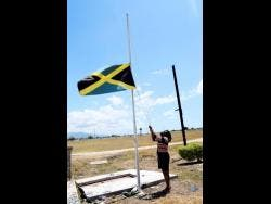 Supreme Ventures General Manager Lorna Gooden hoists the national flag at half mast in mourning for late champion trainer Wayne DaCosta at Caymanas Park in St Catherine yesterday.