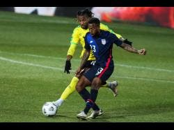 USA's Kellyn Acosta (foreground) duels for the ball with Jamaica's Kasey Palmer during  the international friendly match between USA and Jamaica at SC Wiener Neustadt stadium in Wiener Neustadt, Austria, yesterday.