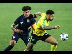USA's Chris Richards (left) duels for the ball with Jamaica's Andre Gray during the international friendly match between USA and Jamaica at SC Wiener Neustadt stadium in Wiener Neustadt, Austria, Thursday, March 25, 2021.