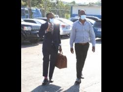 Able-Don Foote (left) and his client George Wright, member of parliament for Central Westmoreland, arrive at the Freeport Police Station yesterday for the questioning session.