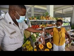 Ermine Reddy sells food items to a member of the Jamaica Constabulary Force.