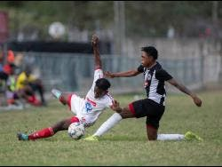Ronaldo Webster (right) of Cavalier FC tackles UWI FC's Nacquain Brown during a  Red Stripe Premier League match between both teams at the Mona Bowl on Sunday February 23, 2020.