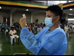 Sasha Johnson, a registered midwife, prepares an Oxford-AstraZeneca COVID-19 vaccine.