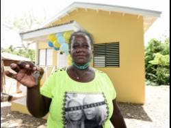 Dawnette Henry shows the keys to her new house in Gayle, St Mary, which was built under the new Social Housing Programme.