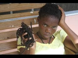Nzinga King, 19, with a handful of her dreadlocks she saved after she was allegedly trimmed by a cop.