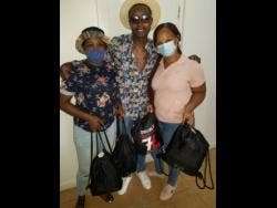 Dancehall artiste Razor B (centre) with two of the recipients.