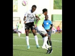 Andre Fletcher (right) of Waterhouse FC is beaten to the ball by Cavalier's Kyle Ming during the Jamaica Premier League final at the UWI-JFF-Captain Horace Burrell Centre of Excellence last  Saturday.  The match ended 1-1 after extra and regulation time and was decided by penalties with Cavalier winning 5-4.