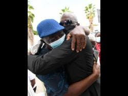 Theo's father Anthony Johnson (right) and uncle Aston Johnson greet each other at his funeral service at Roman's Funeral Home on Dunrobin Avenue, St Andrew yesterday.