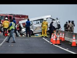 Firefighters and police are observed at the scene of a traffic crash on Highway 2000 in April. Five people died from injuries sustained in the crash.