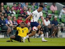 United States' Antonee Robinson (right) moves the ball past Jamaican defender Alvas Powell during last night's Concacaf  World Cup qualifying football  in Austin, Texas. The United States won 2-0.