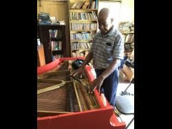 Albert Wellington tunes a piano.