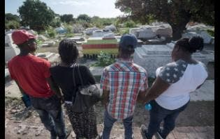 Gladstone Taylor Arlene Reid (second left) and her family members are upset because their relative's body was exhumed from a plot at their home in Mavis Bank, St Andrew, last Friday.