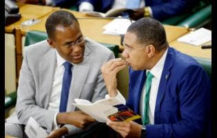 Gladstone Taylor Minister of Finance and the Public Service Dr Nigel Clarke (left) confers with Prime Minister Andrew Holness.