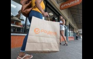 Gladstone Taylor A Payless customer after making a purchase as the Springs Plaza store located on Constant Spring Road in Kingston.