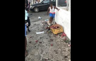 ANDRE WILLIAMS A little boy walks past the fruit and other produce that were said to have been knocked from one of the cars during the accident.