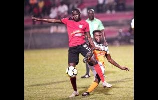 File Arnett Gardens FC's Fabian Reid (left) comes under a challenge from Dunbeholden FC's Clayton Pusey during their Red Stripe Premier League encounter at the Anthony Spaulding Sports Complex on Monday, December 24, 2018.