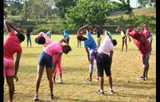 Members of the Holmwood Technical High School Girls athletics team go through a stretch routine at a recent practice session.