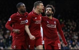 Liverpool's James Milner (centre) celebrates with teammates Georginio Wijnaldum (left) and Mohamed Salah after scoring his side's second goal, during the English Premier League match between Fulham and Liverpool at Craven Cottage stadium in London, yesterday.