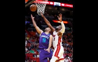 Charlotte Hornets guard Tony Parker (9) goes up to shoot against Miami Heat guard Dwyane Wade (3) during the first half of an NBA basketball game, yesterday.
