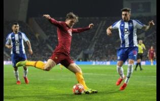 In this Wednesday, March 6, 2019 file photo, Roma's Nicolo Zaniolo shoots the ball in front of Porto defender Alex Telles (right) during the Champions League round-of-16, second-leg match between FC Porto and AS Roma at the Dragao stadium in Porto, Portugal.