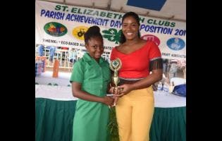 Anthony Foster Alliyah Allen (left) of Siloah Primary receives the St Elizabeth 4-H Clubs Achievement Day 2019 first-place award for Best Project Work Display (junior section) from Miss Jamaica Festival Queen Ackera Gowie.