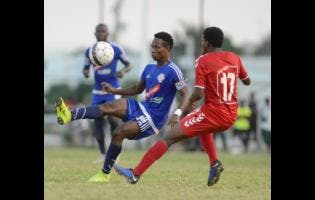 Mt Pleasant's Kemar Beckford (right)  brings the ball under control while being watched by UWI defender Stephen Barnett during the first leg of their Red Stripe Premier League quarter-final at the Anthony Spaulding Sports Complex yesterday. The match ended 2-2.
