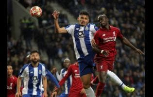 Liverpool's Sadio Mane (right) jumps for the ball with Porto forward Francisco Soares during their second leg UEFA Champions League quarter-final match at Estadio Dragao in Porto, Portugal, yesterday.
