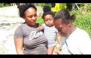 Diana Whitely (right), mother of two year-old Sasha Gaye Dennis, in tears as she related how her young daughter met an untimely death. Her  cousin, Meresa Anderson (with her baby, Rikela Reid), gives a listening ear.