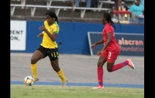Reggae Girl Khadija Shaw (left) in action against Panama's Maria Murilo at the National Stadium on Sunday.