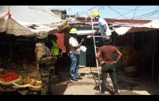 Workmen employed to the Jamaica Public Service Company Limited carry out disconnections on dozens of shops and stalls within the Charles Gordon Market in Montego Bay, on Monday.