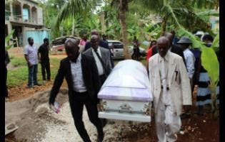 Pall-bearers carry the coffin bearing the remains of Cyslin Brown on Saturday.