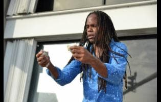 Kenyon Hemans/Photographer Kevin 'Magic One' Williams performs one of his many magic tricks in Half-Way Tree, St Andrew, on Tuesday.