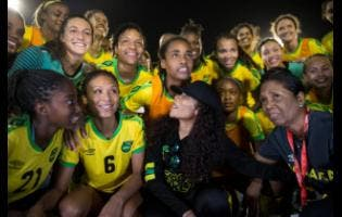 Cedella Marley (centre) hangs out with the Reggae Girlz after their match against Panama at the National Stadium earlier this month.