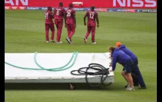 West Indies players go off the field as groundsmen bring on the covers after rain stopped play during the Cricket World Cup warm-up match between West Indies and South Africa in Bristol, England, yesterday.