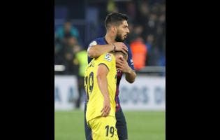 Barcelona forward Luis Suarez embraces Villarreal's Santi Cazorla during the Spanish La Liga soccer match between Villarreal and FC Barcelona at the Ceramica stadium in Villarreal, Spain, Tuesday, April 2, 2019.