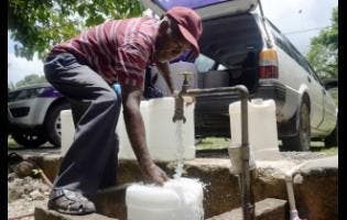 Thomas Douglas, who lives in Coxswain, Clarendon, travels miles away to Suttons in the parish to catch water because the precious commodity is scarce in his community.
