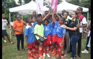 Granville Primary School celebrate its second straight hold on the Victoria Mutual Building Society (VMBS) Under-12 Football Competition title at the UDC field in Montego Bay last Friday.