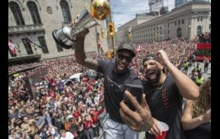 Toronto Raptors' Kawhi Leonard holds his MVP trophy while celebrating with rapper/producer Drake during the team's NBA basketball championship parade in Toronto yesterday.