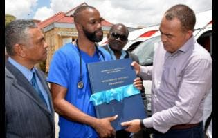 Roosevely Carty (second left), registered physical therapist at the Percy Junor Hospital, shows the new stroke registry to Health and Wellness Minister Dr Christopher Tufton (right) last Thursday. Sharing the moment are Michael Stern (left), deputy chairman of the Southern Regional Health Authority and Dr St Aubyn Bartlett, a member of the board.