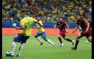 Brazil's Roberto Firmino passes the ball to teammate Gabriel Jesus to score a goal that was disallowed by the referee during a Copa America Group A  match against Venezuela at the Arena Fonte Nova in Salvador, Brazil, on Tuesday.